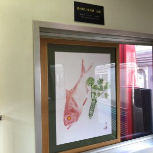 普通乗車券で乗車可能。伊豆急行リゾート21 キンメ電車の3号車のに注目。中村工房の拓技画 を展示中